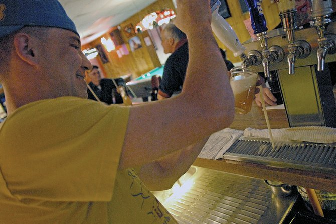 "Brian Garcia, a bartender at Popular Bar, 24 W. Victory Way, prepares drinks for thirsty customers. Craig Daily Press readers voted Popular Bar as the best bar in the 2011 Best of Moffat County contest. Garcia said the bar is a fun watering hole because customers are always treated with respect and people feel comfortable. ""It's a clean, safe place,"" Gacia said. ""There are no fights, no drama."" Dena Garcia, of Craig, has owned the bar for 28 years."