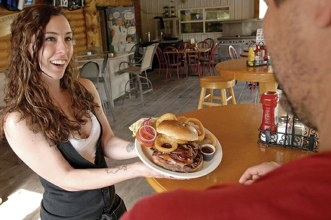 Sabrina Zachary, a server at the O.P. Bar & Grill, 534 E. Victory Way, delivers the restaurant's double burger to a customer in the outdoor seating area. The O.P. took top honors for the best hamburger in Moffat County in the Craig Daily Press' 2011 Best of Moffat County contest. The double burger features a full pound of charbroiled Angus beef, a slice of ham, bacon, barbecue sauce and Swiss and cheddar cheeses. It sells for $10 with a choice of a side.