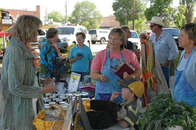Lorrae Moon, center, and Kim Thompson, right, speak with customers at their booth Thursday afternoon at the Craig Farmers Market in Alice Pleasant Park. More than 100 people circulated around the booths in the park throughout the afternoon at the first market of the summer.