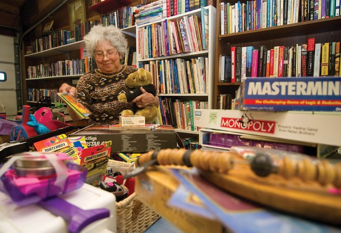 Bargain Barn owner Betty Dickey sorts through a table of stuff in her store at 2780 Acre Lane in Steamboat Springs. Dickey opened the store in August and said things have picked up with the arrival of summer.