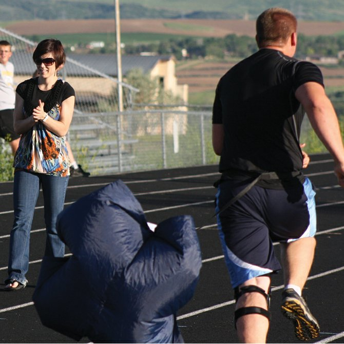 Brandi Babin oversees members of the Moffat County High School football team as they participate in a parachute drill designed to increase running speed with resistance training. Babin, a personal athletic trainer and 2004 MCHS graduate, will be working with the team throughout the summer on improving speed and agility for the upcoming season. Training sessions are also open to members of other athletic teams.