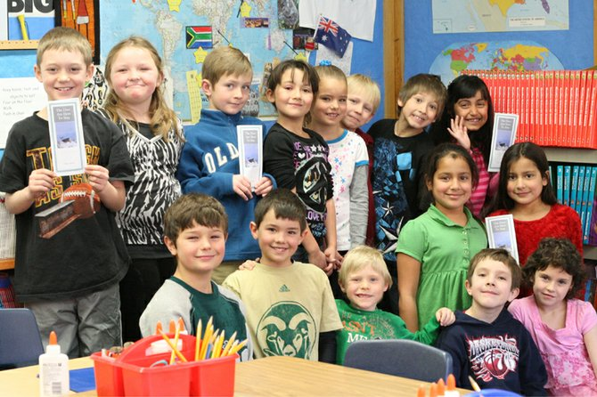 Cheryl Arnett's second-grade students at Sunset Elementary School pose during the 2010-11 school year with copies of the brochure they produced, The Deer Are Here to Stay, regarding the City of Craig's deer population. The brochure will be highlighted in an upcoming national education publication, Smithsonian in Your Classroom.
