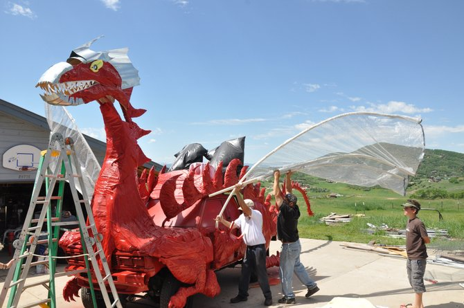 Charlie Holthausen and Dean Ludwick attach a wing to a dragon car Sunday that will be featured in Steamboat's Fourth of July Parade.