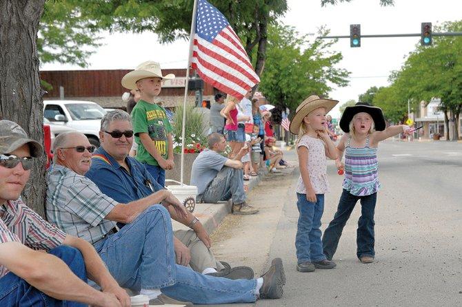 Jolene Rhyne, left, and KatieJo Knez watch the Fourth of July parade with their families Monday on Victory Way. The parade, the first one on the holiday in Craig in numerous years, started at Craig City Park and made a loop on Victory Way, Yampa Avenue and Sixth Street before ending back at the park.