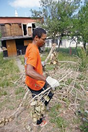 Jason Raeburn performs yard work Wednesday at the old Simmons Rooming House in the 700 block of Yampa Avenue. Raeburn, of Beacon, N.Y., is one of 28 volunteers for the Fuller Center for Housing who are cycling across the U.S. The group left Seattle on June 12 and plans to arrive Aug. 13 in Washington, D.C.