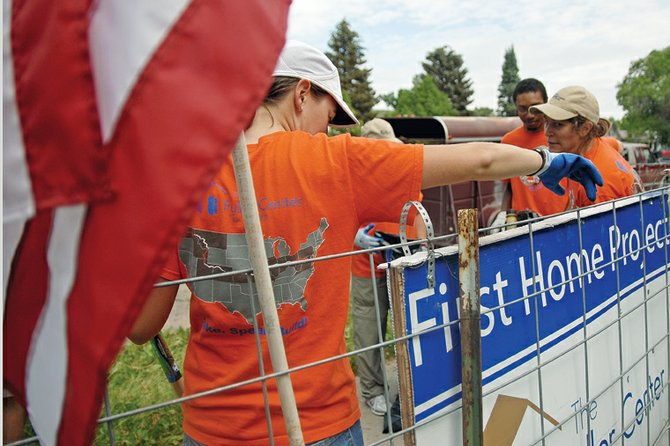 Volunteers for the Fuller Center gather Wednesday outside the Simmons Rooming House on Yampa Avenue. Twenty-eight volunteers for the Fuller Center are cycling across the United States and performing community services along the way.