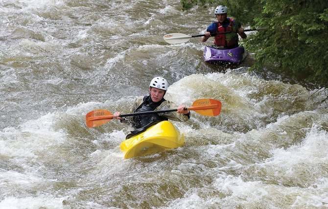 Chris Schell, left, and Timmy Schell kayak down Fish Creek near Safeway on Friday afternoon. Recent storms have pushed Fish Creek, along with the Yampa and Elk rivers, to record levels for July 8.