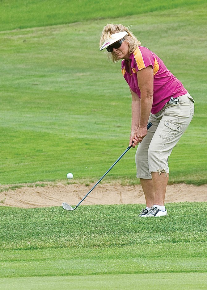 Karen Campbell chips at the 12th annual Rally for the Cure Golf Tournament on Tuesday at Rollingstone Ranch Golf Club.