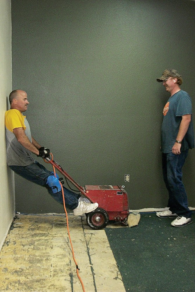 Volunteer workers Andy Saulpaul, left, and Cody McCarthy remove old carpeting from the Craig Chamber of Commerce. The Chamber is in the midst of a remodeling project , which will be completed in time for the organization's annual mixer at 5 p.m. Thursday.