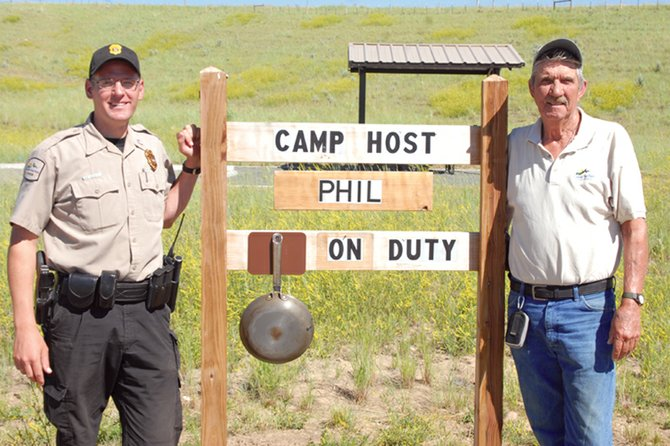 Senior State Park Ranger Matt Schuler, left, and Phil Poucher lean against Poucher's campsite sign at Elkhead State Park. Poucher, of Longmont, is spending the summer as the campground host at Elkhead, a volunteer job that grants him a free set-up at the park in exchange for performing area maintenance and assisting campers when needed.