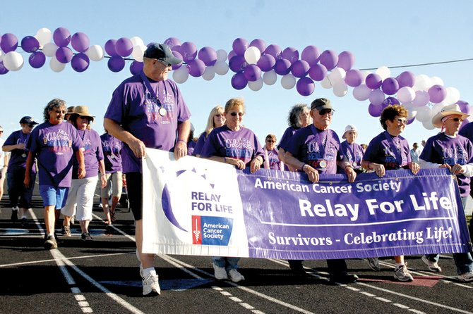 Cancer survivors lead the way during the Yampa Valley Relay for Life's survivors' lap Friday evening at the Moffat County High School track. At the beginning of the event, organizers announced that funds raised exceeded $20,000. Organizers will continue raising money through the end of August.