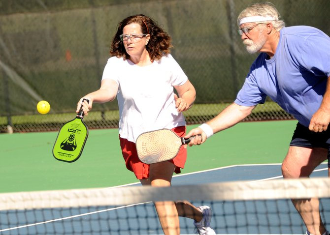 Mary Lou Gallup and Jay Readinger rush for a return Friday while playing pickleball on the tennis courts at the base of Howelsen Hill in Steamboat Springs. The pair learned the sport in Florida, where it's hugely popular in senior citizens communities, and is trying to help it catch on in their new home of Steamboat.