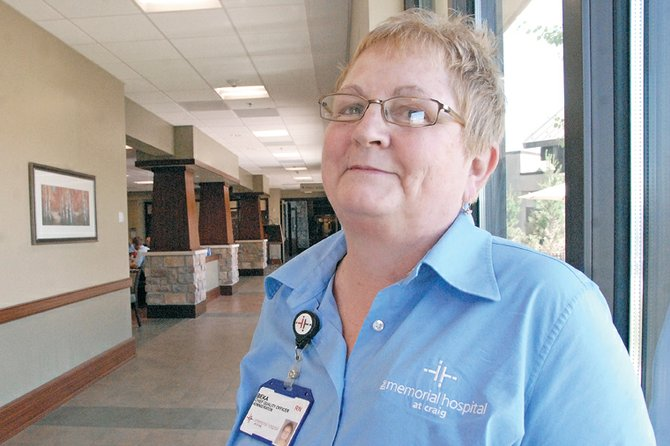 Beka Warren, chief quality officer for The Memorial Hospital and deputy coroner for Moffat County, stands Wednesday near the administration offices at TMH. Warren, a registered nurse, has taken college courses in varying fields during nearly every semester of her adult life.