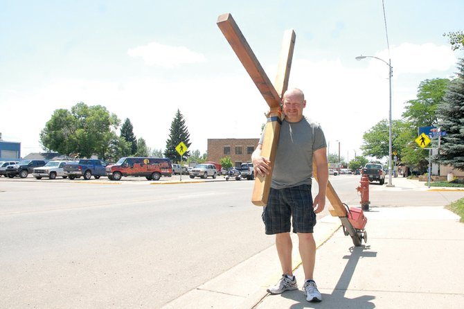 Mike Rumsour, of Missouri, stands Monday along Victory Way with a cross he and a friend built over his shoulder. Rumsour started traveling with his cross in March from the Golden Gate Bridge as part o