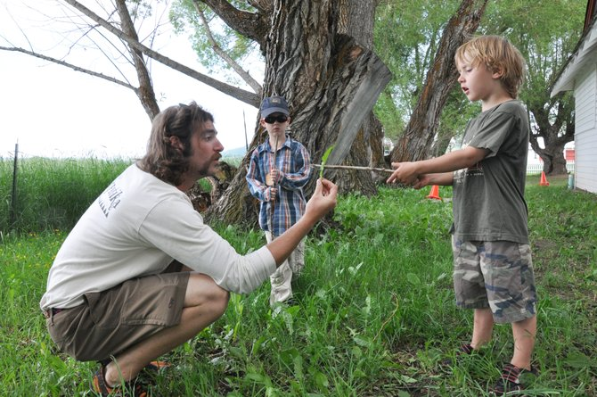 Yampatika is hoping the U.S. Congress passes the No Child Left Inside Act, which would fund environmental education programs across the country. Above, Yampatika summer naturalist Kevin McGarity, left, holds out a leaf for Sam Kitchen to examine at the Environmental Learning Center at Legacy Ranch.