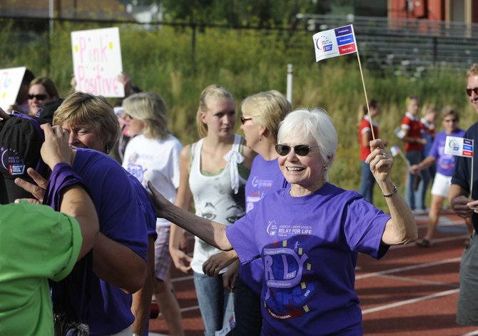 Breast cancer survivor Doris Ross, of Florida, waves a flag during the Relay For Life survivor lap in 2010. This year's event kicks off Friday at the Steamboat Springs High School track.