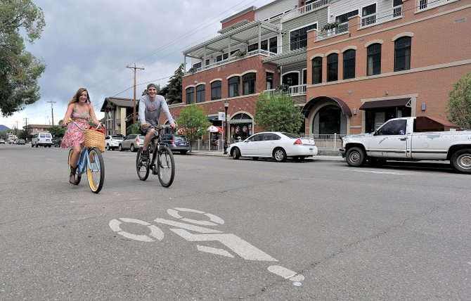 Taze Henderson and Missy Krause ride their bikes along Yampa Street in downtown Steamboat Springs. The city of Steamboat Springs plans to install designated bike lanes on Yampa Street next week and also has added signs to designate shared use on roads.