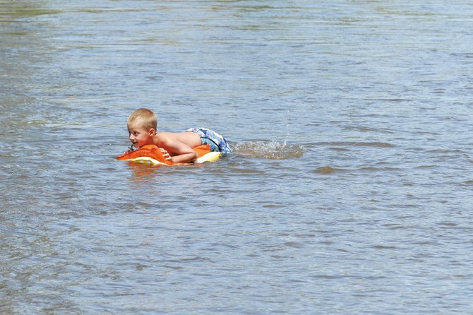 Caden Call, 7, floats Friday in the Yampa River off Pebble Beach while enjoying time with his friends and family. The river's water levels have gone down considerably since reaching dangerous numbers in May. However, flow is still well above average, and officials warn recreational users to be extremely cautious.