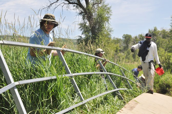 Sky Strang, left, helps remove the handrail of a bridge near the Carpenter Ranch in Hayden. Strang is one of three high school students from New York who arrived in the Yampa Valley earlier this month to work at the ranch during a monthlong internship.