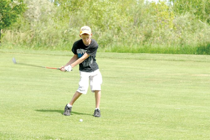 Cole Hoth, 14, prepares to make contact with his ball Monday on the 13th hole during the Yampa River Junior Classic at Yampa Valley Golf Course.
