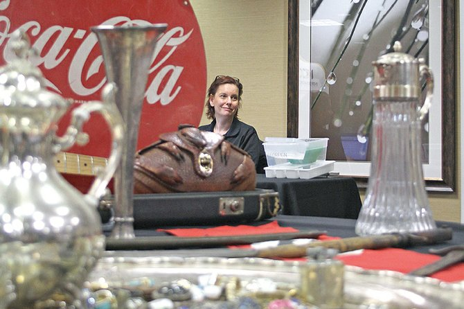 Joan Landquist, a buyer for the International Coin Collectors Association, sits amid numerous displayed antiques during an April show at Craig's Hampton Inn. ICCA is an associate of Treasure Hunters Roadshow, which will host a show beginning at 9 a.m. today at the Holiday Inn of Craig. While ICCA is more focused on pricing and buying rare coins, THR seeks out antiquities of all sorts, including artwork, jewelry, toys and other items.