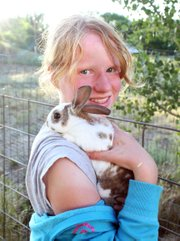 Emma Balstad holds Bucky on her shoulder July 20 at her home in Maybell. Emma said she hopes to be an animal breeder when she grows up and that breeding her rabbits in 4-H is teaching her about the trade.