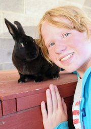 Emma Balstad, 12, poses with her rabbit, Quill, on July 20 at her home in Maybell. Emma will show Quill and other rabbits in August at the Moffat County Fair.