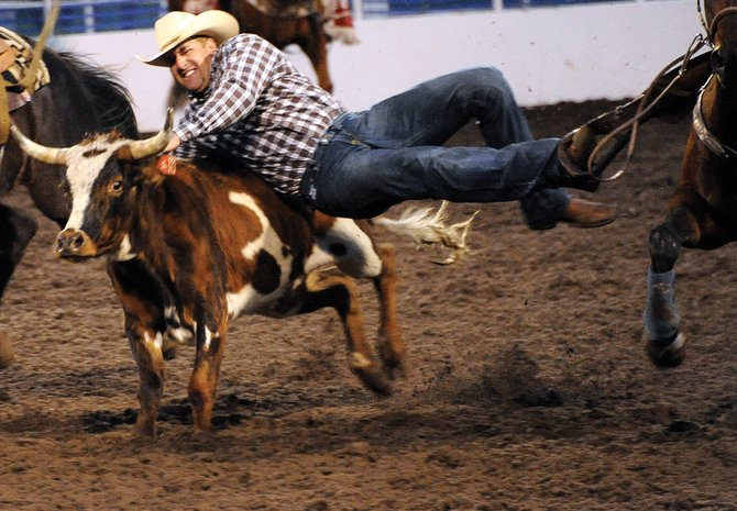A steer wrestler flies in for the takedown earlier this year at the Steamboat Springs Pro Rodeo series. The 10-weekend event returns at 7:30 p.m. tonight at Romick Rodeo Arena in downtown Steamboat Springs for its seventh go-around this summer.