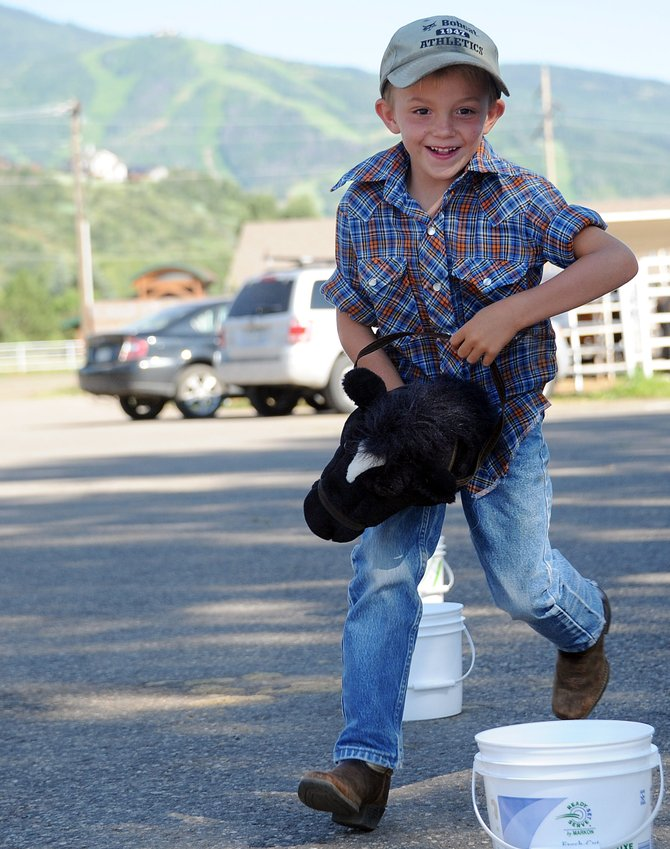 Levi Allen, 6, from Steamboat Springs, races around buckets in stick-horse races on Saturday at Brent Romick Rodeo Arena in Steamboat Springs during the Ranch Rendezvous event.
