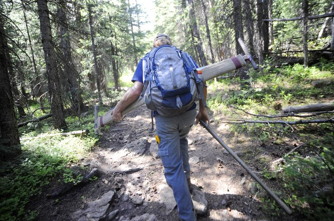 Yampa Ranger District backcountry trail crew member Justin Benson hikes into the Flat Tops Wilderness Area carrying a 5 1/2-foot cross-cut saw used to clear timber in the wilderness, where only primitive tools are allowed.