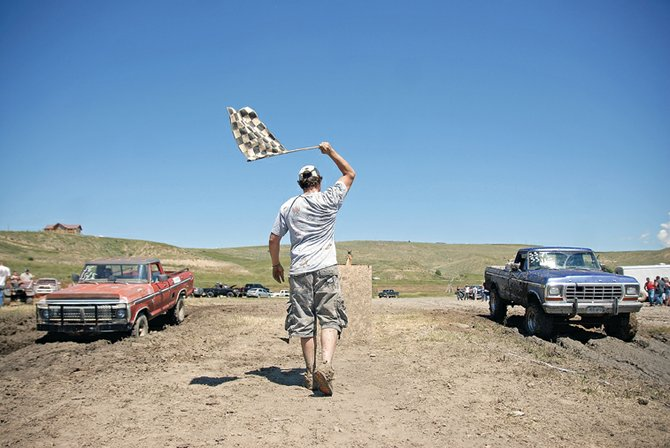 Craig resident Jason Vallejos drops the flag to start a race Saturday during the 2011 Moffat County Mud Runs at Wyman Museum. Gunning their engines are Meeker resident Loren Maybury, left, in a 1973 Ford pickup with a 390 engine, and Craig resident Greg Merrick, in a 1978 Ford pickup with a 460 engine.