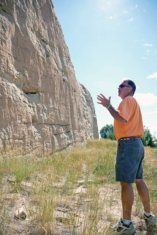Dave Pike, Craig Parks and Recreation director, points Thursday toward petroglyphs on the Sandrocks in Craig. Pike said the city might develop a trail system above the cliffs. Trail improvements below the rocks are less certain.