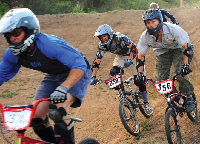 The men of the 30-plus Rookie category of Thursday's BMX race in Steamboat Springs — from left, Jon Freckleton, Jim Kohler and Chip Ellis — race at the year-old course set up at the base of Howelsen Hill. The event was the fifth in a 10-race series planned for the track this summer. While some of the evening's riders knew how to navigate the course quickly, others were attacking it for the first time.