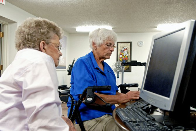 Clarene Yonkers, left, a resident of Sunset Meadows in Craig, watches fellow graduate and neighbor, Dottie Reynolds, start up her new computer. Both women received computers Wednesday by completing Learn and Earn, a computer literacy program for seniors and those with disabilities.