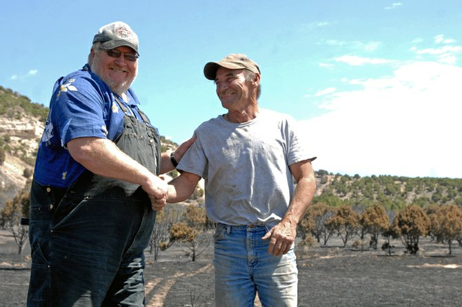 John Stehle, left, who lives on Cedar Mountain Avenue, shakes hands with friend Phil Pinnt with burnt trees and ash at the base of Cedar Mountain in the background. Pinnt alerted authorities to the Cedar Fire on Tuesday. Stehle said a quick response to the blaze saved his home.