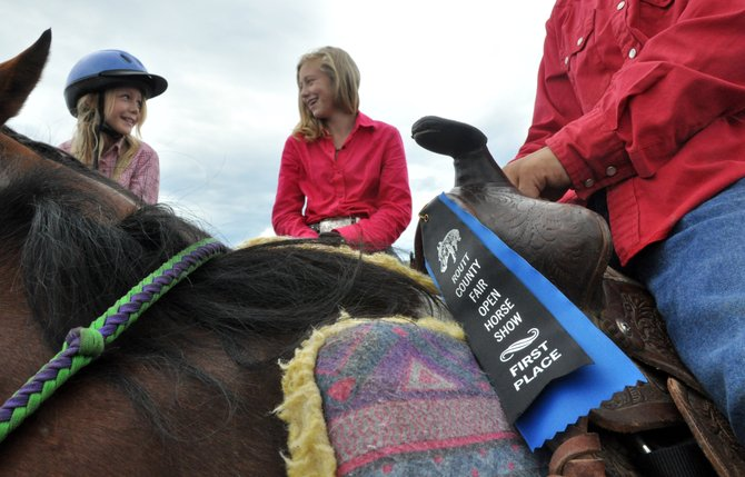 Paige Barnes, left, and Kaitlyn Hayes wait to compete in a round of an open horse show Sunday at the Routt County Fairgrounds in Hayden as Keenan Hayes holds the first place ribbon he won at the competition earlier in the day. Sunday's horse show was one of several events leading up to the opening of the Routt County Fair on Thursday.