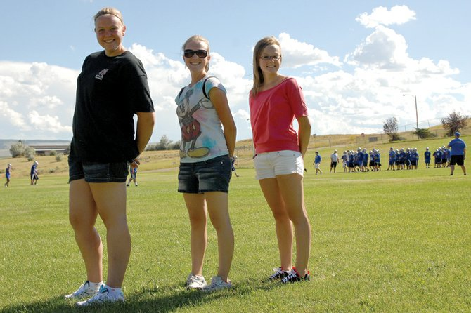 Jordan McLeslie, left, stands on the Moffat County High School football practice field with Erica Dilldine, middle, and Jordan's sister, Kristina McLeslie. Jordan, an incoming MCHS senior, is the athletic trainer for the MCHS football, basketball and girls soccer teams. She hopes to pursue the program in college.