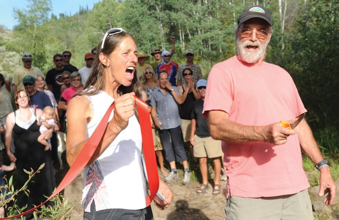 Ben Beall, right, and Gretchen Sehler celebrate as Beall cuts the ribbon on the Emerald Mountain trail named after him. Beall was instrumental in a land swap that helped preserve much of Emerald Mountain, a 13-year process that helped lead the way to the construction of Beall Trail and several other trails in the area.