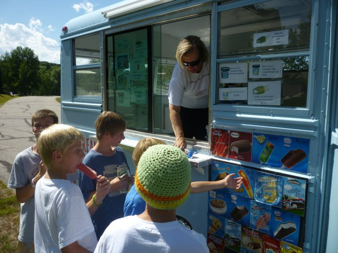 Buffalo Gal Ice Cream & Goodies owner Ruth Abate sells treats to a group of boys Wednesday afternoon. Abate resumed operating the ice cream truck in mid-July after starting the business last fall.