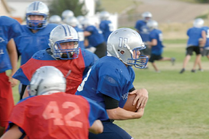 Bubba Ivers, a Moffat County High School junior, runs up the middle during an MCHS varsity football team practice this week. Ivers, the team's starting quarterback, will lead the Bulldogs into their first game tonight at Evergreen High School. Evergreen defeated MCHS, 26-22, in last season's opener.