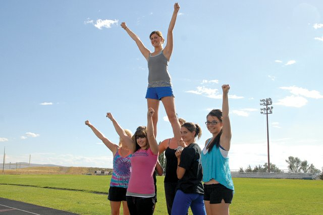 The Moffat County High School spirit team practices stunts Wednesday on the MCHS track. New head coach Jennifer Vallem said she wants to help bring recognition to the program by having them participate in competitive cheering events this year.