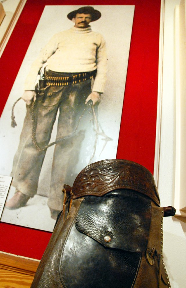 "A pair of chaps made by ""Bad Bob"" Meldrum sits on display at the Museum of Northwest Colorado. In the background is a photograph taken of him while he was working as a guard for Telluride mine workers in the early 1900s. Meldrum's career included stints as a Pinkerton agent, marshal, union strikebreaker and range detective. His life and exploits are featured in a new book about Colorado's history of outlaws."