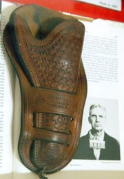 "A holster made by ""Bad Bob"" Meldrum sits atop a book with Meldrum's prison photo at the Museum of Northwest Colorado. While serving as marshal around Baggs, Wyo., Meldrum fatally shot Chick Bowen, an area cowboy, in 1912. Meldrum was imprisoned for the crime."