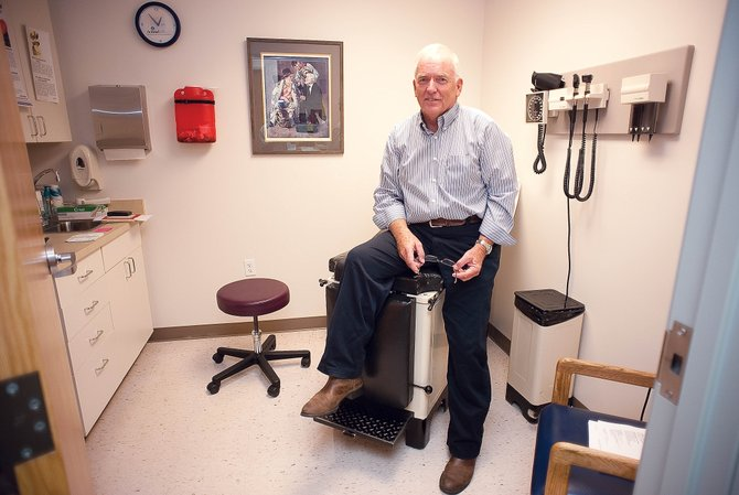 Dr. Lambert Orton's exam room reflects his passion for serving the community. The exam table was his father's, and in the background you can see a painting of a country doctor treating patients. Orton looks up to the ideals represented by the country doctor and keeps that in mind when he treats his patients in Steamboat Springs. This year, his work and dedication to the community will be rewarded with the Doc Willett Award.