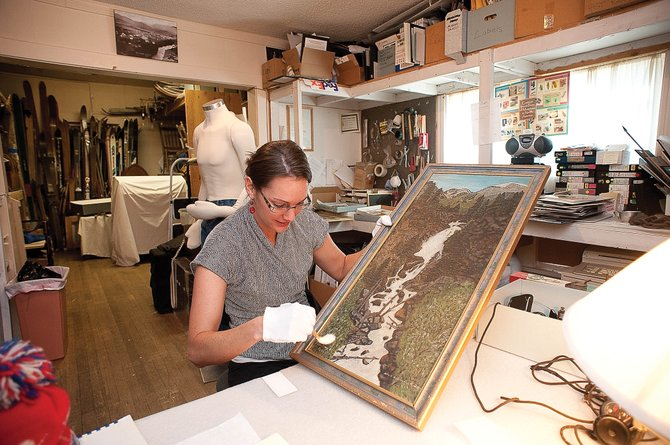 Tread of Pioneers Museum curator Katie Adams cleans a painting of Fish Creek Falls by longtime Steamboat resident Mary Zimmerman before cataloguing the item and storing it in the museum's current storage area. The museum is hoping to build a climate-controlled storage area for the collection.