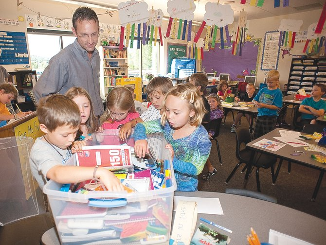 George Avgares, director of Colorado Student Care, distributes school supplies in Maggie Moore's second grade classroom at Strawberry Park Elementary School on Wednesday morning. Avgares collected the supplies with help from Partners in Routt County, Routt County United Way and Alpine Bank.