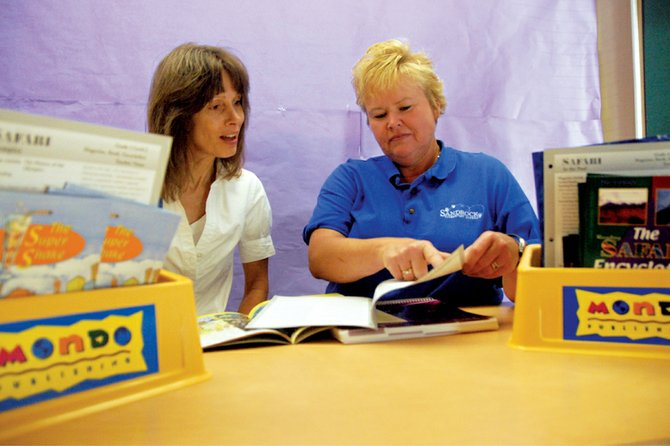 Vera Turner, left, half-time literacy coordinator at Sandrock Elementary School and half-time gifted and talented coordinator for Moffat County School District, and Stephanie Davis, the school's full-time literacy coordinator, look through reading materials Friday morning at Sandrock. This year, all elementary schools in the district have full-time literacy coordinators.