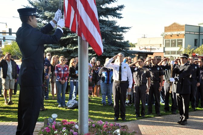 Steamboat Springs firefighter Bobby Davis lowers a flag Sunday as a crowd salutes and looks on in front of the Routt County Courthouse during a ceremony commemorating the 10th anniversary of the Sept. 11, 2001, terrorist attacks.