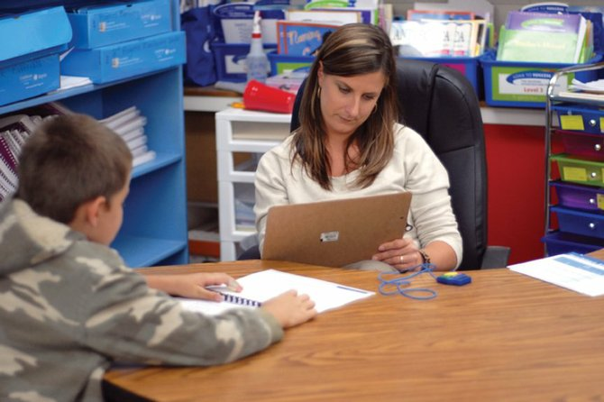 Third-grader Sabastian Hershiser reads aloud during a Dynamic Indicators of Basic Early Literacy Skills test while Deb Durbin, a special education/Title I paraprofessional, listens Monday afternoon at Sandrock Elementary School. DIBELS and other tests issued in the fall can help teachers evaluate where their students stand academically at the beginning of the school year.