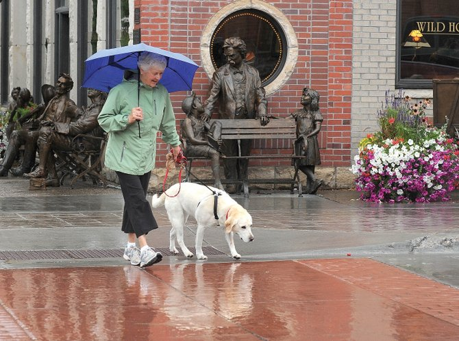 Mary Lou Fahres and her dog Shasta walk through the rain in downtown Steamboat Springs on Thursday morning. Residents of Steamboat Springs woke up to cooler, wet weather Thursday, a sure sign that fall has arrived in the Yampa Valley.